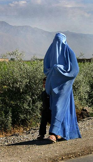 A woman with burqa on walking with a child by ...