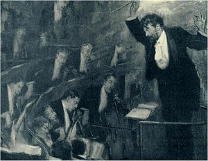 bearded man in evening dress seen from his left, conducting an orchestra and making a dramatic gesture, holding the baton high over his head