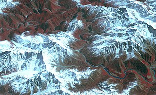 The Yarlung Tsangpo Grand Canyon from space, viewed from a somewhat oblique angle. The Yarlung Tsangpo river is seen coursing through the tall, sharp peaks of snow-capped mountains.