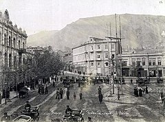 A picture of a city square with people walking about and people riding in carriages.