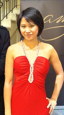 Yuja Wang in a shoulder-free red dress, looking at the camera