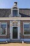 foto van Koopmanshuis D'Mol. Grotendeels houten huis in L-vorm. Brede bakstenen voorgevel met geblokte hoeklisenen en in het midden een rijk versierde ingangspartij met Ionische pilasters.