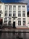 foto van Huis met gebosseerd gepleisterde gevel met schuiframen en ingangspartij bestaande uit geblokte pilasters met kroonlijst waaronder triglyphen met druppen