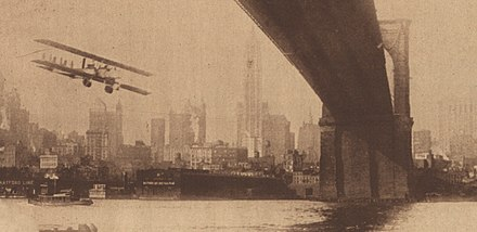 A Caproni biplane flies under the Brooklyn Bridge 1919-newyork-biplane-bridge.jpg