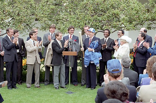 Howser (to left of podium) presents President Ronald Reagan with a Royals jacket, hat, and bat at the White House after their World Series victory. 1985 Kansas City Royals at White House.jpg