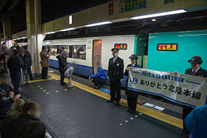 "Hokuetsu - JR staff holding a ""Thank you"" banner on the platform at Kanazawa Station prior to the departure of the final Hokuetsu service to Niigata on 13 March 2015"