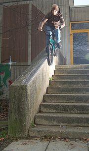 ein BMXer rutscht auf seinen Pegs eine Mauer herunter, im BMXer-Jargon ein so genannter 50-50-Grind