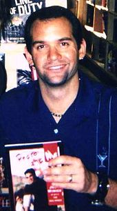 Photograph of Judd Winick of The Real World: San Francisco holding a copy of his novel, Pedro and Me