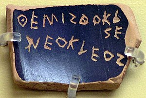 Attic Greek - A ballot voting against Themistocles, son of Neocles, under the Athenian Democracy (see ostracism). The text is an example of the epichoric alphabet; note that the last two letters of Themistocles are written in a boustrophedon manner and that E is used for both long and short e.