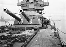 A twin-barrelled gun turret on a large warship, photographed by someone standing near the bow. Anchor chains are in the foreground, and the superstructure of the ship can be seen behind the turret.