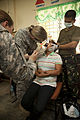A U.S. Army medical officer, center left, performs a dental procedure for a resident during a cooperative health engagement (CHE) at Inhobol Elementary School in Masinloc, Zambales province, Philippines 130405-M-UY788-127.jpg