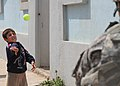 A U.S. Soldier from 214th Military Police (MP) Company, plays catch with a local boy in the northern town of Al Koosh, Iraq, May 3, 2011 110503-A-RH393-305.jpg
