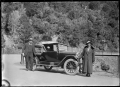 A chevrolet motor car parked at Elbow Bend on the Mount Cargill to Waitati road, with a man and woman standing beside. ATLIB 294014.png