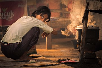 A girl set fire to cook breakfast by using a coal-filled clay pot; July 2014.jpg