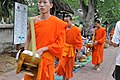 A young monk walks by without expression (14603845434).jpg
