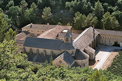 In a wooded valley is a large church with small windows and a square stone belfry. It is surrounded by ancient buildings arranged around courtyards, and a lavender garden.