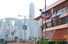 street shot showing blue and red advertising banners on street lamps with the words 'Act Now', Hong Kong's skyline in the background