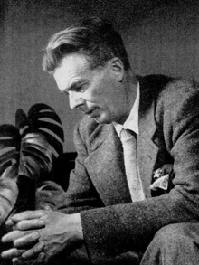 Monochrome portrait of Aldous Huxley sitting on a table, facing slightly downwards.
