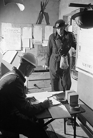 Air Raid Precautions in the United Kingdom - An ARP Warden (in overalls) reports for duty to the Chief Warden at his sector post in Springfield, Essex, August 1941.