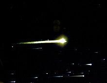 Witte strepen van licht, met heldere vlekken op de rechterkant van hen, vul de onderkant van het frame.  Een grotere geelgetinte bol met een strook in het midden van het kader.  De achtergrond is zwart ruimte.