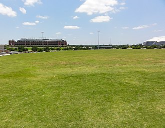Arlington Stadium - A large portion of the stadium's site is now occupied by an empty field, pictured in 2012. Globe Life Park in Arlington and AT&T Stadium are visible in the background.