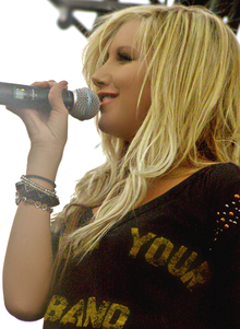 A young blonde female singer on a stage sings into a microphone.