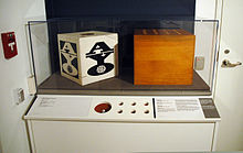 A museum exhibit comprising a table, in the corner of a room between a door with a fire alarm handle, with a glass case on top containing two wooden boxes with holes in the top. The front of the table comprises a printed description of the exhibits within the case and several holes, simulating the artworks within the case.