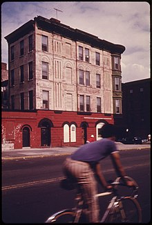 BICYCLIST PASSES AN EXAMPLE OF BROOKLYN ARCHITECTURE ON VANDERBILT AVENUE IN NEW YORK CITY. BROOKLYN REMAINS ONE OF... - NARA - 555894.jpg