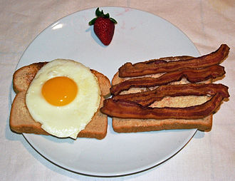 Bacon - Bacon and egg on toast, garnished with a strawberry