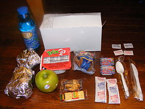 """A-ration - Marine Corps-issued A-ration, colloquially known as a """"bag nasty"""" or a """"box nasty,"""" as this one is delivered in a nondescript white """"box."""" This example contains two breakfast sandwiches, cereal, crackers with peanut butter and jam, a muffin, fresh fruit, and a drink."""