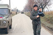 A young man wearing battledress and a beret with a Serbian flag badge stands on a road and holds an AK-47 rifle.