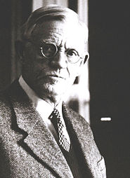 An elderly man with parted white hair, small round glasses, dressed in a tweed suit and tie