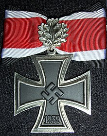 a colour photograph of a metal cross with a ribbon
