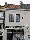 foto van Pand met verdieping en dwars zadeldak. Gepleisterde voorgevel met in de verdieping twee vensters met zesruitsschuiframen
