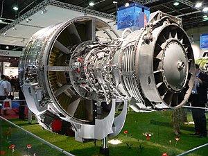 An exposed jet engine at a trade show. The rear of the polished metal fan case is visible on the left. The outer casing of the compressor section, covered in fuel lines and electrical wires is in to the right of the fan case. The right of the image shows the back of the engine, the exhaust area of the turbine section.