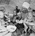 COLLECTIE TROPENMUSEUM Een oudere Samo vrouw pelt samen met kinderen aardnoten TMnr 20010227.jpg