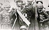 Indonesische Soldaten posieren im November 1975 im osttimoresischen Batugade mit einer erbeuteten portugiesischen Flagge