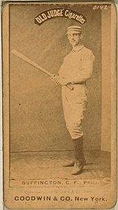 A baseball player is standing, facing the camera, holding a baseball bat.