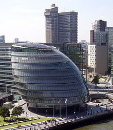 Nine-story rounded glass building beside river.