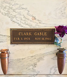 Marble crypt with brass plaque inscribed: Clark Gable, Feb. 1. 1901 Nov. 16. 1960. Two vases are attached to the crypt, one contains a purple rose.