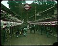 Crowd-filled street lined with banners and lanterns. (19329403923).jpg