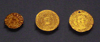 Photograph of three crusader coins from the British Museum. Left: A Denier in European style with Holy Sepulchre (1162–75). Centre: a Kufic gold bezant (1140–80). Right: gold bezant with Christian symbol (1250s). Gold coins were first copied dinars and bore Kufic script, but after 1250 Christian symbols were added following papal complaints