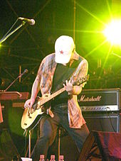 Close-up of a man onstage with a guitar wearing jeans and a baggy shirt. His head is lowered and his face is obscured by a white hat with a red star on it. In the background is musical equipment.