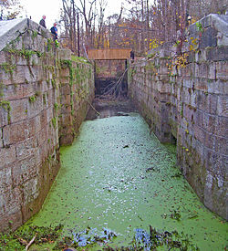 Water with green algae on top in a narrow depression between two stone retaining walls. Two men are looking into it from the upper left.