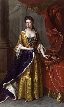 Anne in blue and yellow robes. The Crown Jewels are on a table to her left.
