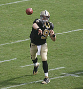 A light-skinned man throwing a football