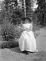 En gammal kvinna i vitt förkläde och rutig blus sitter framför en blomrabatt - Nordiska Museet - NMA.0057476.jpg