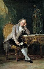 Portrait of a man seated at a desk, cheek resting on his hand