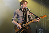 Colour photograph of Franz Ferdinand lead singer Alex Kapranos performing live in 2008.