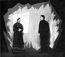 A black-and-white photo of a man and woman on a stage